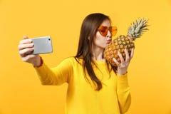 Jovem mulher bonito nos óculos de sol posse, beijando o fruto do abacaxi que faz o selfie disparado no telefone celular isolado n imagens de stock royalty free
