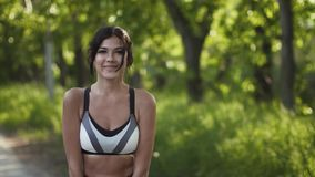 Jovem mulher bonito nova no sportswear que levanta e que sorri na câmera o atleta da menina difunde a beleza e a saúde filme
