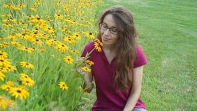 Jovem mulher bonito que cheira flores amarelas em um canteiro de flores no parque vídeos de arquivo