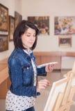 Jovem mulher bonito que pinta uma imagem perto de uma armação em um estúdio fotografia de stock