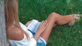 Jovem mulher bonito que senta-se na grama e que lê o livro filme