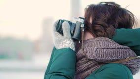 Jovem mulher bonito que toma a imagem Jovem mulher bonita que toma imagens na cidade no inverno filme