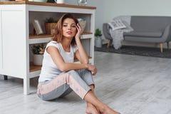 A jovem mulher bonito senta-se no assoalho na cozinha e em apreciar a manhã Mulher vestida no sportswear ocasional fotos de stock