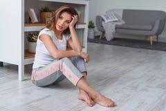 A jovem mulher bonito senta-se no assoalho na cozinha e em apreciar a manh? Mulher vestida no sportswear ocasional fotos de stock