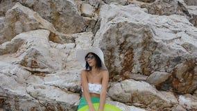 Jovem mulher bronzeada no biquini branco, nos óculos de sol e no chapéu grande com o colchão perto da rocha alta pelo mar Férias  vídeos de arquivo