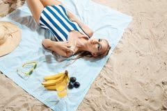 Jovem mulher bronzeada que toma o sunbath insalubre em um dia de verão em uma praia que esconde do sol com chapéu e vidros de pal imagens de stock royalty free