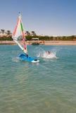 A jovem mulher cai a placa para o windsurfe em Egito, Hurgha Fotos de Stock Royalty Free