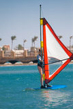 A jovem mulher cai a placa para o windsurfe em Egito, Hurgha Fotos de Stock