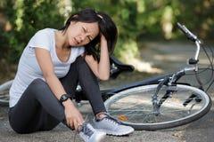 A jovem mulher caiu a bicicleta na floresta imagens de stock royalty free