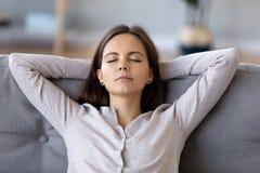 Jovem mulher calma com mãos atrás da cabeça que relaxa em casa foto de stock royalty free