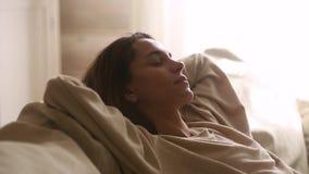 Jovem mulher calma que manda a sesta saudável relaxar no sofá video estoque