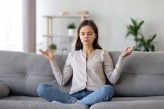 Jovem mulher calma que senta-se na pose dos lótus no sofá, meditando em casa imagem de stock