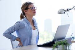 Jovem mulher cansado com dor nas costas usando seu portátil em casa Imagens de Stock