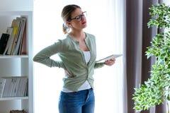 Jovem mulher cansado com dor nas costas usando sua tabuleta digital em casa fotos de stock