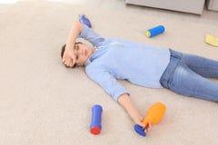 Jovem mulher cansado que encontra-se no tapete cercado por fontes de limpeza fotografia de stock royalty free