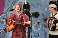 A jovem mulher canta músicas e joga a balalaica Fotos de Stock Royalty Free