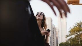 Jovem mulher caucasiano atrativa feliz com os sacos de compras nos óculos de sol que olham acima, usando o smartphone app em New  video estoque