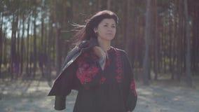 Jovem mulher caucasiano atrativa na posição preta e vermelha longa bonita do vestido na conexão da floresta do pinho com video estoque