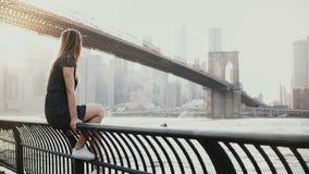 Jovem mulher caucasiano bonita que senta-se na cerca da terraplenagem do rio na ponte de Brooklyn New York, jetski que passa por  video estoque