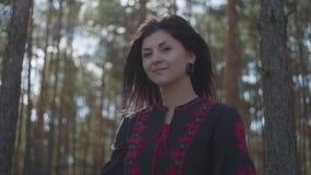 Jovem mulher caucasiano bonito na posição preta e vermelha do vestido na floresta do pinho que olha à câmera Conex?o com a nature filme