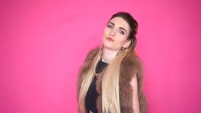 Jovem mulher caucasiano glamoroso em uma dança à moda do casaco de pele e vista da câmera, isolada no fundo cor-de-rosa vídeos de arquivo