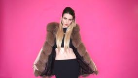 Jovem mulher caucasiano glamoroso em uma dança à moda do casaco de pele e vista da câmera, isolada no fundo cor-de-rosa filme