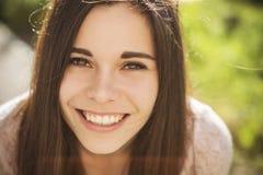 Jovem mulher caucasiano moreno bonita que laughting mostrando o perfe fotografia de stock