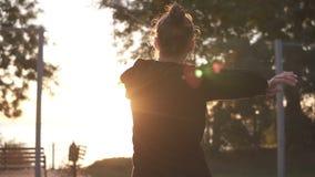 Jovem mulher caucasiano que aquece-se na manhã no campo de básquete Esticando seus braços antes do treinamento do basquetebol video estoque