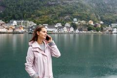 A jovem mulher chamou acima com seu Smartphone com um fiorde em Noruega imagens de stock royalty free