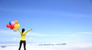 Jovem mulher Cheering com os balões coloridos no pico de montanha Imagens de Stock