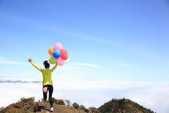 Jovem mulher Cheering corrida com balões Foto de Stock
