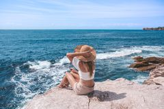 Jovem mulher chique que senta-se pelo oceano foto de stock