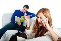 Jovem mulher chocada em algo no telefone enquanto seu noivo lê Imagens de Stock