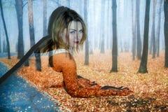 Jovem mulher coberta com a imagem da floresta do outono fotografia de stock