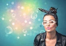 Jovem mulher com óculos de sol e luzes coloridas do bokeh Fotografia de Stock