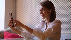 A jovem mulher com airpods recebe a chamada video filme