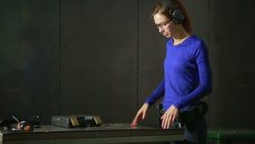 Jovem mulher com a arma em uma escala de tiro interna recolha a arma filme