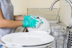 Jovem mulher com as luvas que lavam pratos fotografia de stock royalty free