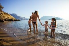 Jovem mulher com as quatro crianças que andam nas águas do mar imagens de stock royalty free