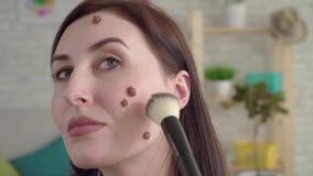 Jovem mulher com as toupeiras em sua cara que olha no espelho e que faz a composição filme