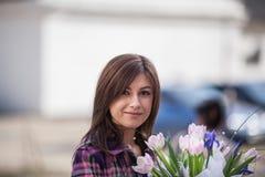 Jovem mulher com as tulipas nas mãos Foto de Stock