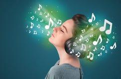 Jovem mulher com auscultadores que escuta a música Foto de Stock