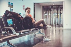 Jovem mulher com a bagagem que espera no salão do aeroporto seu plano Imagens de Stock