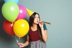 Jovem mulher com balões e ventilador do partido no fundo da cor Celebração do aniversário Imagens de Stock