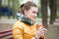 Jovem mulher com bebida quente no parque Foto de Stock