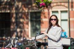 Jovem mulher com a bicicleta em férias europeias em Amsterdão Imagens de Stock Royalty Free