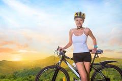 Jovem mulher com bicicleta em uma estrada da montanha Fotos de Stock Royalty Free