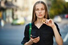 Jovem mulher com bitcoin da moeda e smartphone à disposição na parte traseira imagem de stock