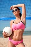 Jovem mulher com bola do voleibol e rede na praia Fotografia de Stock Royalty Free