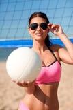Jovem mulher com bola do voleibol e rede na praia Foto de Stock